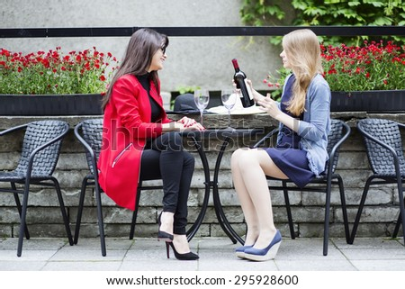 Friends chatting and drinking wine in cafe - stock photo