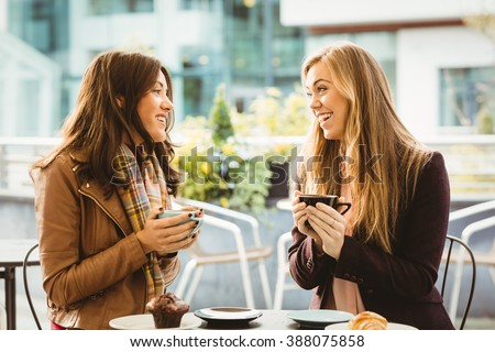 Friends chatting over coffee in cafe - stock photo