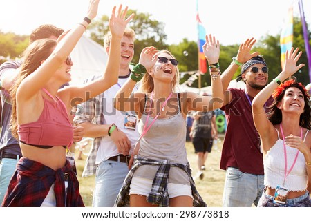 Friends cheering a performance at a music festival - stock photo