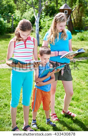 Friends children reading books outdoors on grass