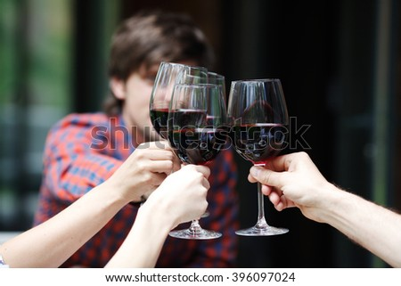 Friends clink glasses of red wine at outdoor dinner