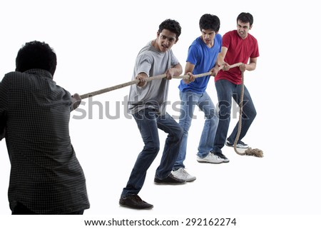 Friends competing in game of tug of war together over white background - stock photo