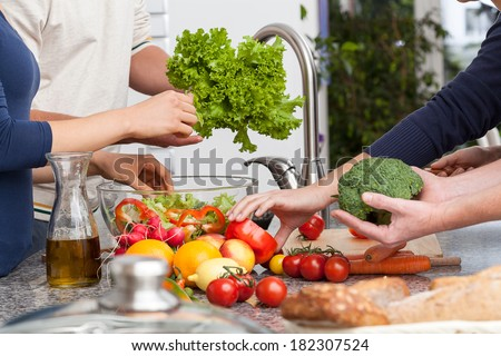 Friends cooking together the veagetarian dinner in kitchen - stock photo