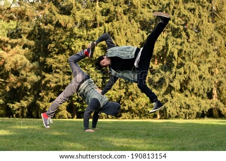Friends dancing break dance in the park - stock photo