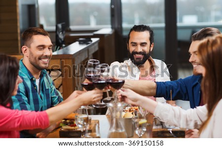 friends dining and drinking wine at restaurant - stock photo