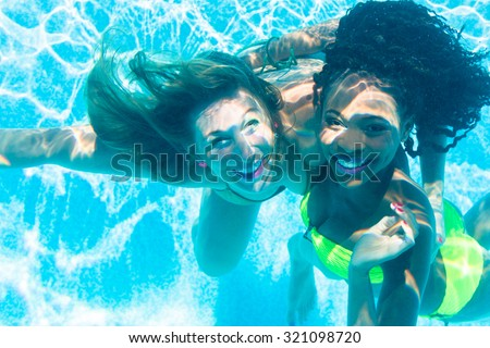 Friends diving underwater in swimming pool, black and white girl - stock photo