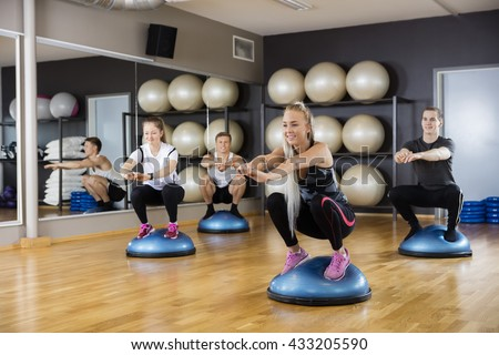 Friends Doing Squatting Exercise On Bosu Ball In Gym - stock photo
