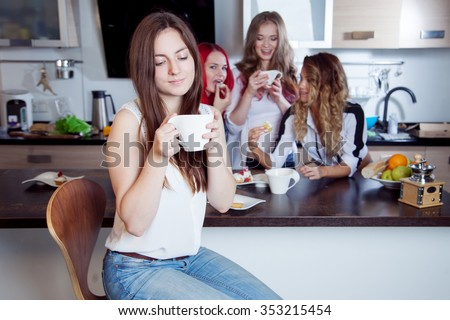 friends drink tea and coffee at kitchen, portrait of  young beautiful brunette in the foreground, woman with white cup - stock photo