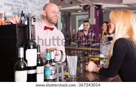Friends drinking and chatting with cheerful adult barman at bar counter - stock photo