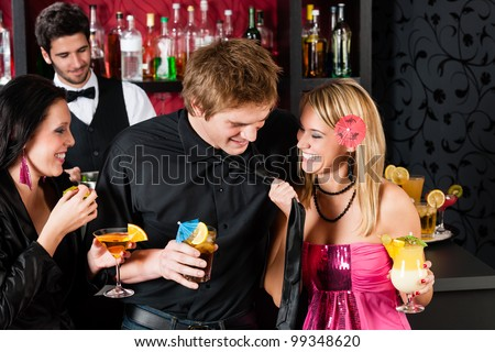 Friends drinking at cocktail bar during happy hours have fun - stock photo