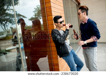 Friends drinking beer and talking outdoors - stock photo