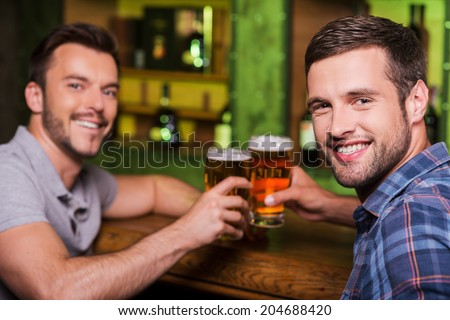 Friends drinking beer. Two cheerful young men toasting with beer and smiling while sitting together at the bar counter  - stock photo