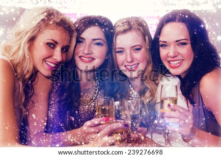 Friends drinking champagne against gold and red lights - stock photo