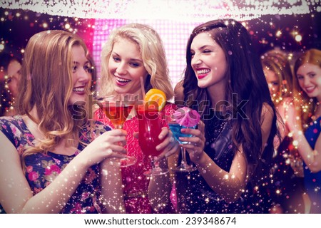 Friends drinking cocktails against gold and red lights - stock photo