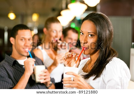 Friends drinking milkshakes in a bar and have lots of fun; focus on the woman in front - stock photo