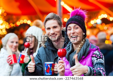 Friends drinking mulled wine and eating crystalized apples on German Christmas Market - stock photo