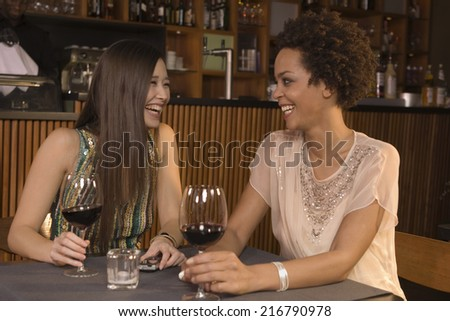 Friends drinking wine at a restaurant. - stock photo