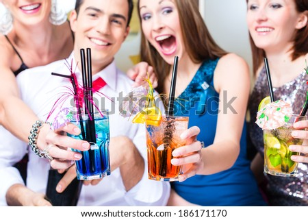 Friends drinking with barkeeper cocktails in fancy night club  - stock photo