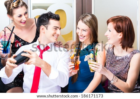 Friends drinking with barkeeper cocktails in fancy night club