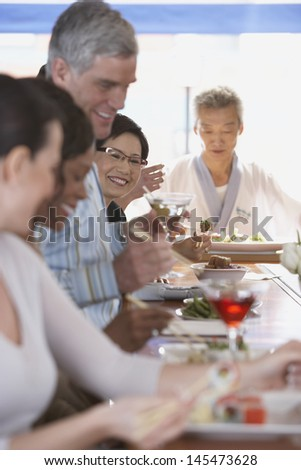 Friends eating and drinking at bar - stock photo