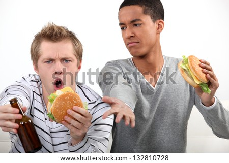 Friends eating hamburgers and watching a football game - stock photo