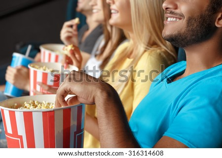 Friends eating popcorn at the movie theatre - stock photo
