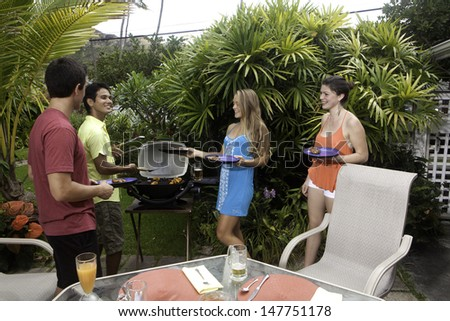 friends enjoying a barbecue lunch in a tropical garden