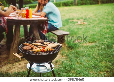 Friends enjoying barbecue time in the nature. - stock photo