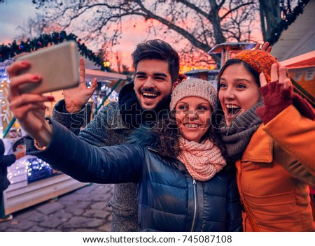 Friends Enjoying Christmas Market And Making Selfie