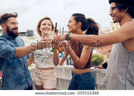 Friends enjoying cocktails at a party. Friends having fun and drinking cocktails outdoor on a rooftop get together. Group of friends toasting drinks outdoors. - stock photo