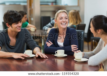 Friends enjoying coffee together in college cafe - stock photo