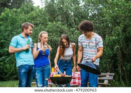 Friends enjoying picnic day and making barbecue together.
