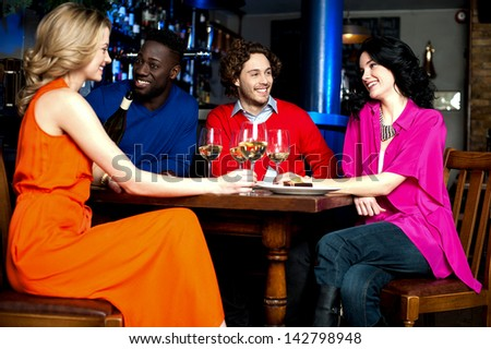 Friends enjoying their dinner with drinks at a restaurant. - stock photo