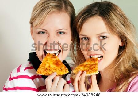 Friends enjoying their slice of pizza - stock photo