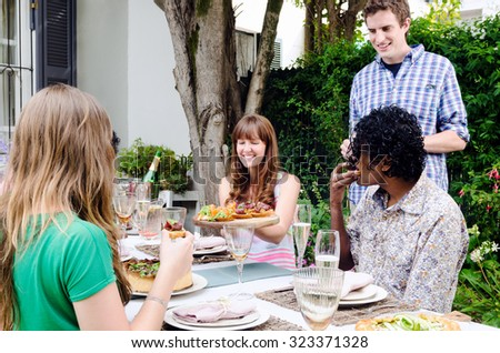 Friends enjoying themselves and having fun at a party with food and alcohol, a casual lunch get together in a garden