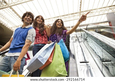 Friends enjoying while shopping at mall - stock photo