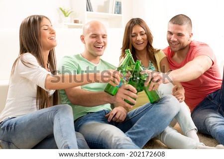 Friends enjoying with beer and cheers together at home party.