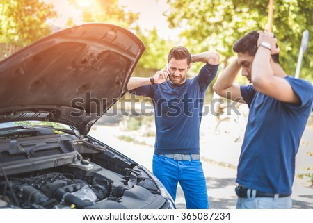 Friends examining broken down car on sunny day - stock photo