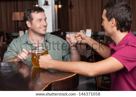 Friends forever. Two friends drinking beer at the bar - stock photo
