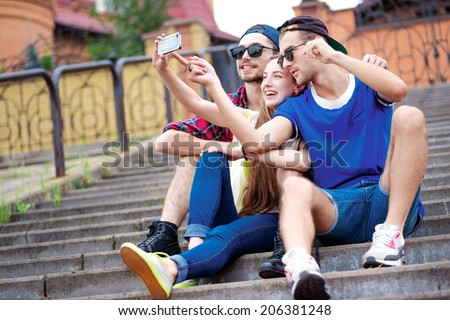 Friends forever. Young friends have fun together on the street and smile at each other. Funny guys make Selfie - stock photo