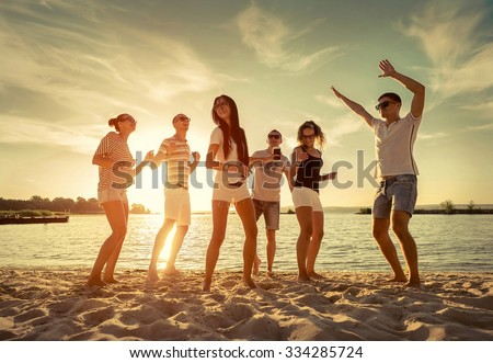 Friends funny dance on the beach under sunset sunlight. - stock photo