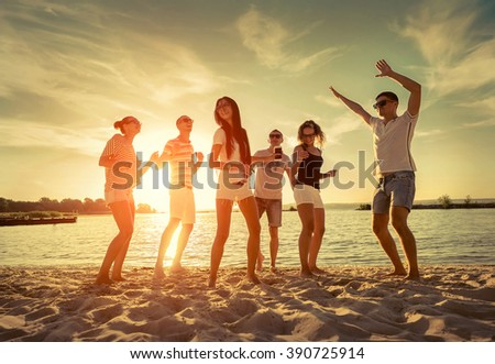 Friends funny dance on the beach under sunset sunlight. - stock photo