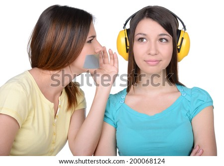 Friends gossip. Two beautiful young women gossip, standing isolated on white. One girl with headphones so as not to hear the other with closed mouth