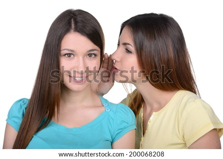 Friends gossiping. Two beautiful young women gossiping while standing isolated on white
