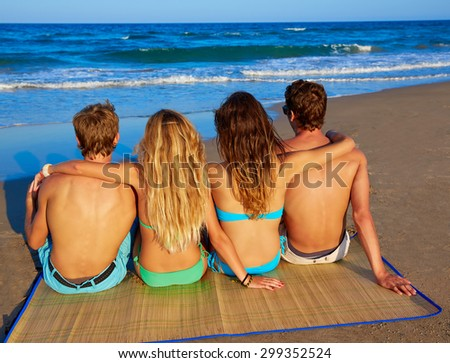 friends group couples sitting in beach sand rear view back looking to the sea - stock photo