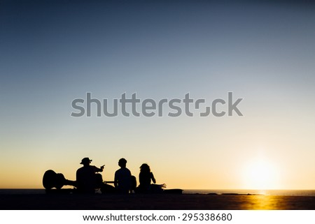 Friends group playing guitar in sunset near the sea
