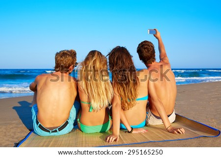 friends group selfie photo sitting in beach sand rear back view - stock photo