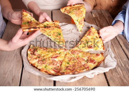 Friends hands taking slices of pizza - stock photo