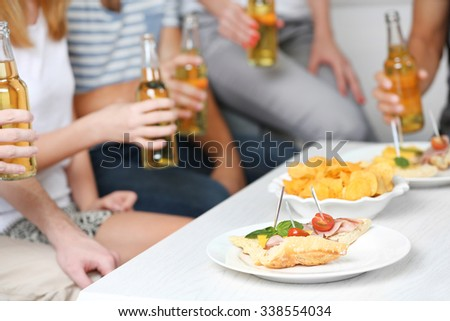 Friends hands with bottles of beer and snacks , close up