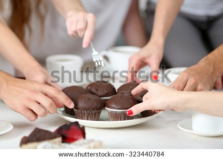 Friends hands with desserts and cups of tea, close up - stock photo